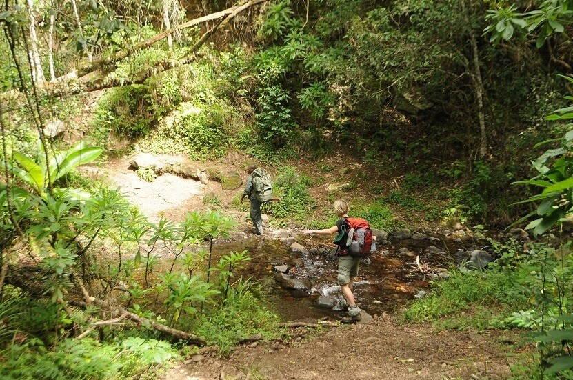 Twee mensen steken het water over door over stenen te lopen